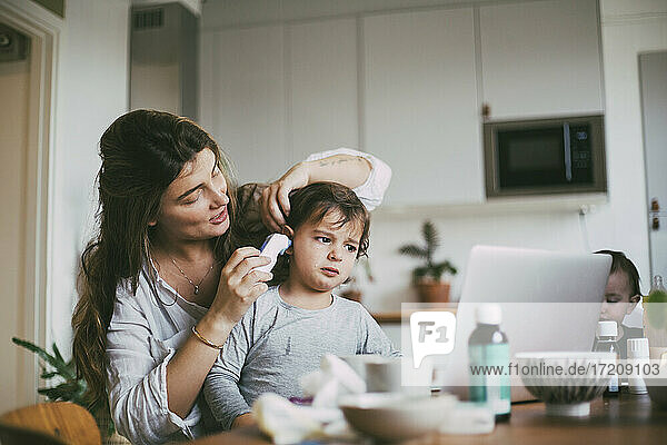 Mother checking son's ear through otoscope at home