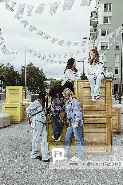 Female friends spending leisure time by box container on footpath in city
