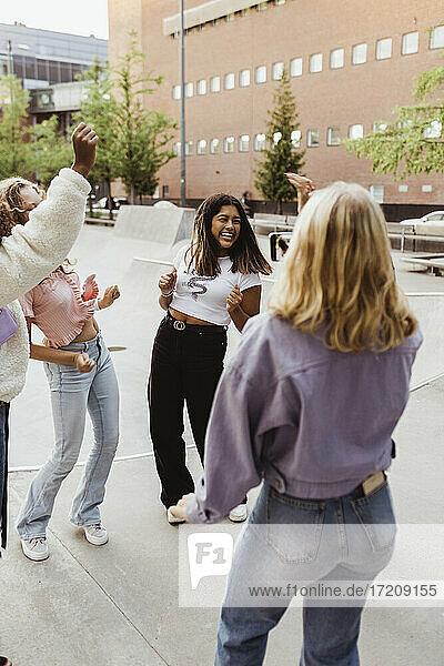 Happy female teenager friends dancing at skate park