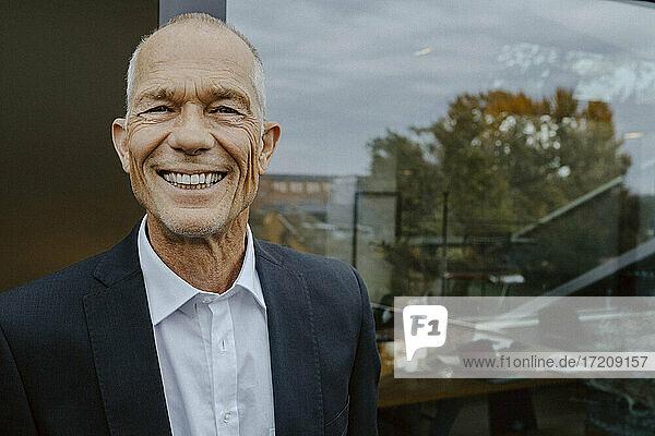 Portrait of smiling male entrepreneur outside office