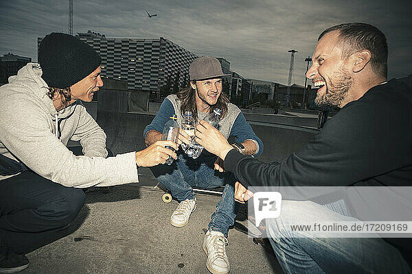 Male friends laughing while sitting at skateboard park