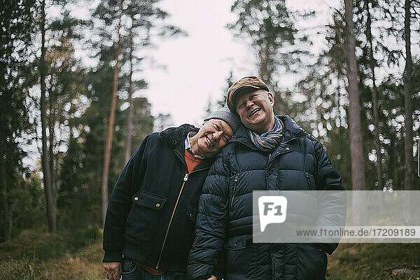 Portrait of smiling gay couple standing in forest
