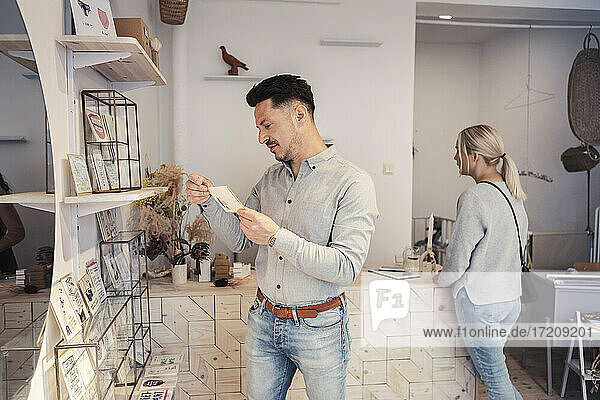 Male customer looking at greeting card while standing by woman in design studio
