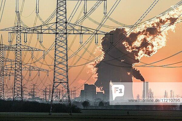 Stromtrasse zum Braunkohlekraftwerk Niederaußem der RWE Power AG bei Sonnenuntergang  Sinnersdorf  Nordrhein-Westfalen  Deutschland  Europa