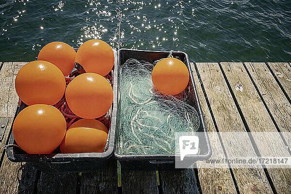 Auf einem hölzernen Steg stehen zwei Kunststoff-Kisten mit orange-farbenen Plastik-Bojen  Tauen und einem Fischernetz. AUf dem Wasser glitzert die Frühlingssonne
