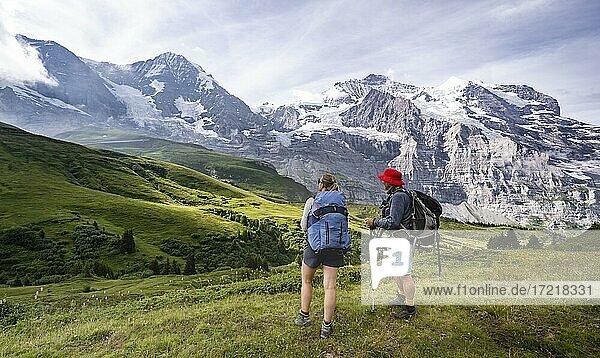 Zwei Wanderer vor der Eiger Nordwand  Steilwand und Berge  Jungfrauregion  Lauterbrunnen  Berner Alpen  Schweiz  Europa
