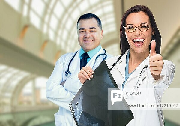 Doctors or nurses with thumbs up holding x-ray standing inside hospital