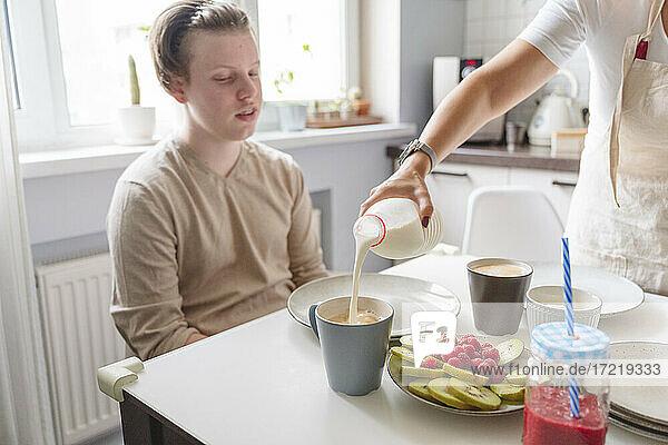 Frau gießt Milch in Tasse für Sohn im Teenageralter am Esstisch in der Küche