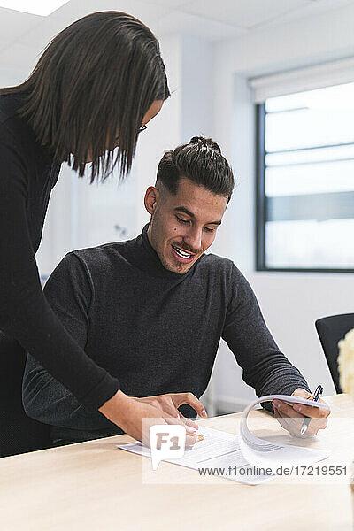 Unternehmerin bei der Vertragsunterzeichnung durch einen männlichen Kollegen am Schreibtisch im Büro