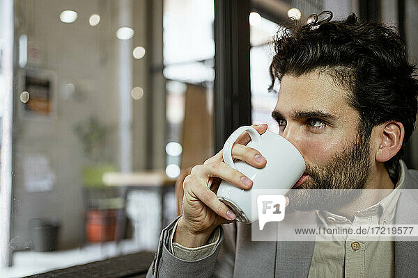 Male freelancer drinking coffee in illuminated cafe
