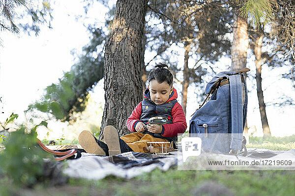Unschuldiger Junge spielt mit einem Vergrößerungsglas an einem Rucksack in einem öffentlichen Park