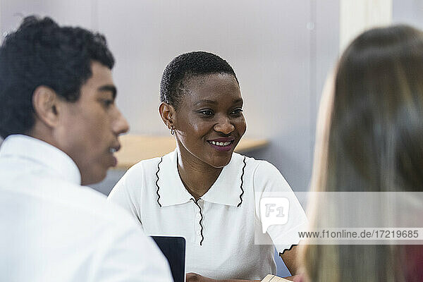 Smiling businesswoman in meeting with colleagues at workplace