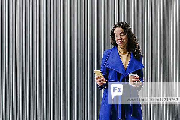 Beautiful female professional using smart phone while having coffee in front of striped wall