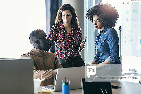 Businessman discussing over laptop with female colleagues at office