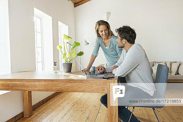 Mann sitzt am Schreibtisch mit Laptop und sieht seine Freundin im Büro an
