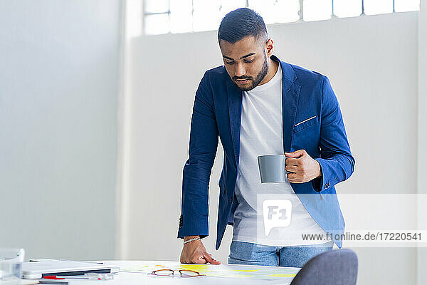Handsome businessman with coffee cup looking at strategy at office