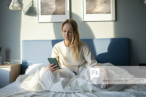 Frau benutzt Mobiltelefon  während sie zu Hause auf dem Bett sitzt