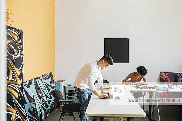 Hipster-Mann mit Laptop  während junge Frau am Tisch im Studio übt