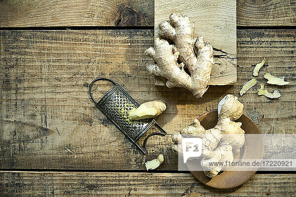 Ginger roots and old grater lying on wooden surface