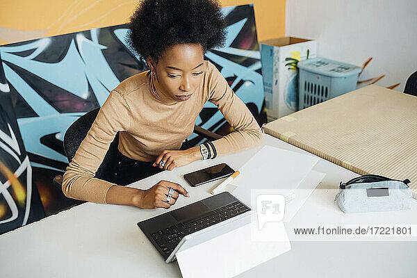 Junge Afro-Frau  die einen Laptop benutzt und am Tisch im Studio sitzt