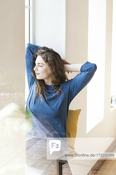 Young woman with eyes closed relaxing at window in living room