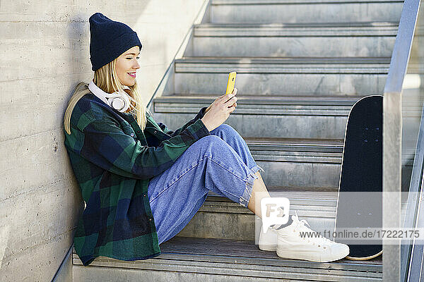 Smiling woman in knit hat using mobile phone on steps