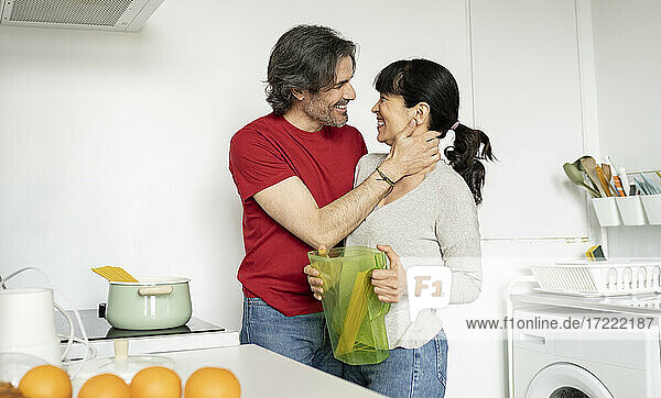 Man embracing woman holding jug while standing in kitchen at home