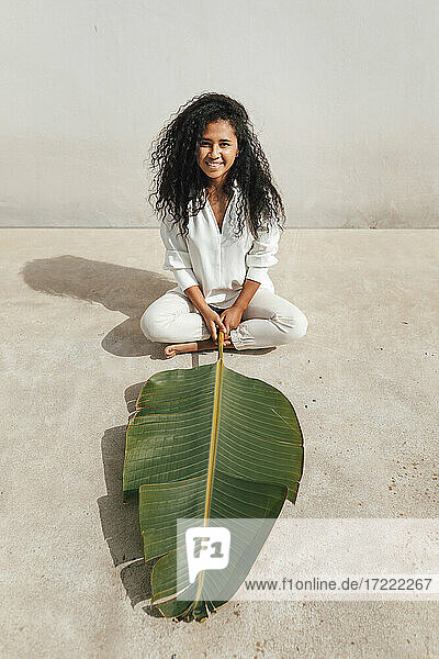 Smiling curly haired woman with green banana leaf sitting cross legged in front of white wall during sunny day