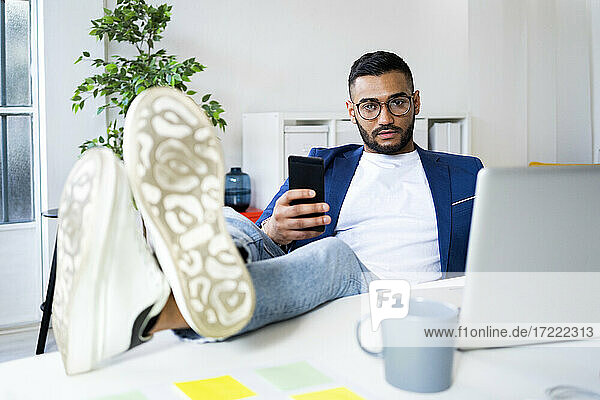 Businessman with smart phone relaxing with feet up on desk at office