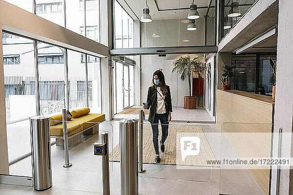 Geschäftsfrau mit Gesichtsschutzmaske benutzt Ausweis am Drehkreuz beim Betreten eines Büros
