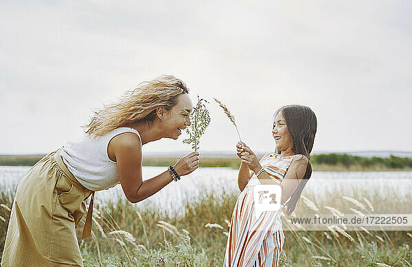 Playful mother and daughter holding twigs by lake