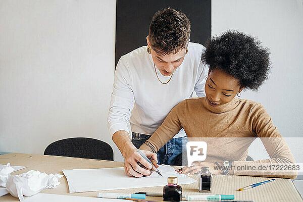 Junger Mann hilft Freundin beim Üben von Kalligraphie im Atelier