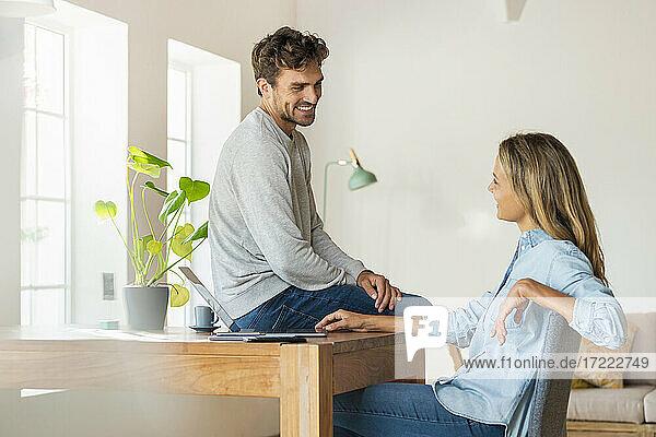 Lächelndes Paar  das sich gegenseitig anschaut  während es auf einem Schreibtisch mit Laptop im Büro sitzt