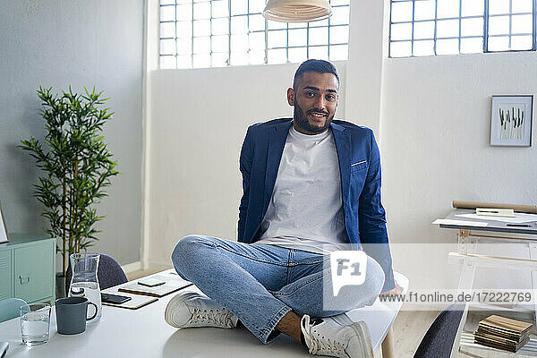 Businessman with cross-legged sitting on desk at office