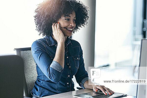 Smiling female customer service representative talking through headphones at desk in office