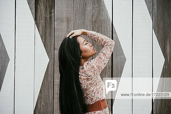 Beautiful woman with head in hand standing by wooden wall