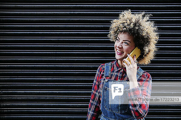 Cheerful woman talking on smart phone in front of shutter