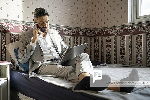 Geschäftsmann mit Laptop  der zu Hause mit einem Mobiltelefon spricht