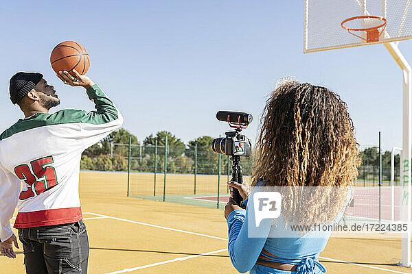 Female filming male friend playing basketball on sports court