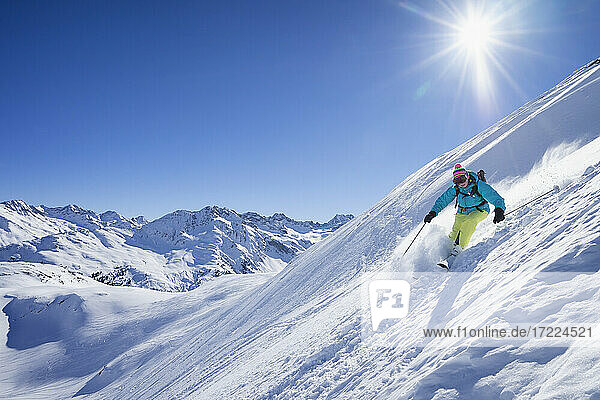 Sun shining over woman skiing in Arlberg massif
