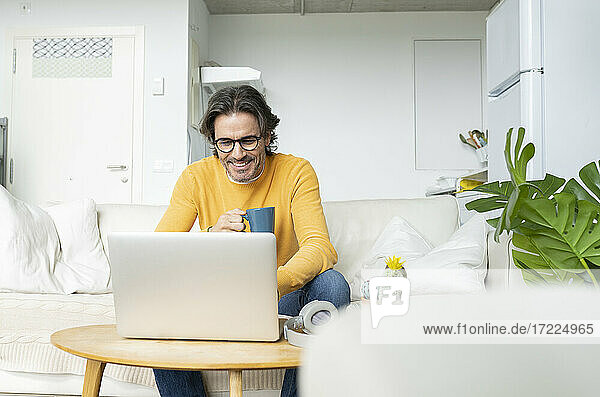 Smiling man holding mug while using laptop at home