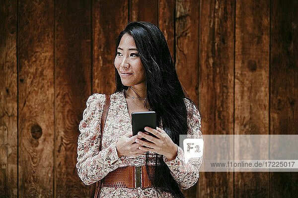 Woman with smart phone looking away while standing by wooden door