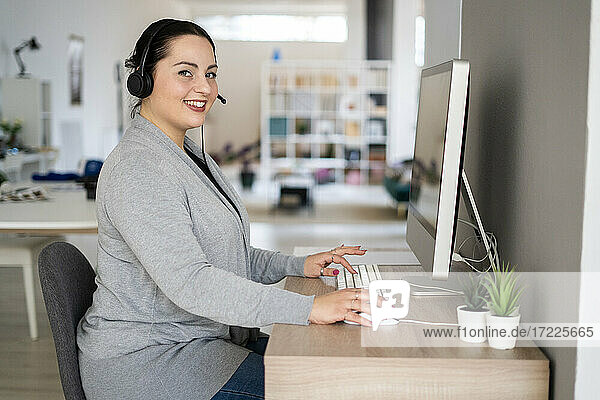 Smiling female customer service representative using computer while working at home office