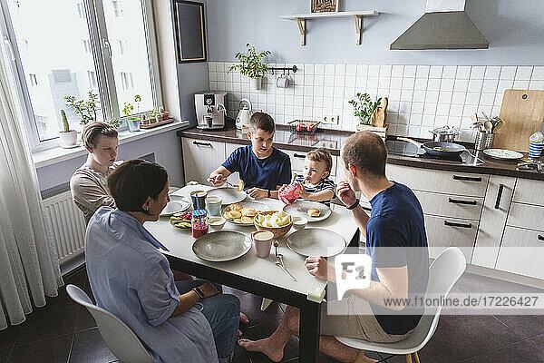 Glückliche Familie beim Essen am Esstisch in der Küche zu Hause