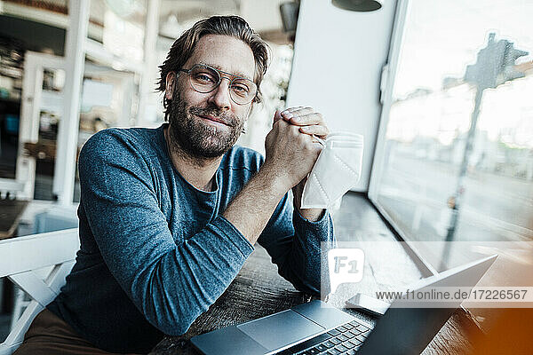 Smiling confident man by laptop in coffee shop during COVID-19