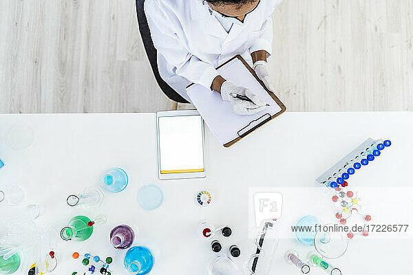 Eine Forscherin schreibt auf einem Klemmbrett im Labor auf Papier