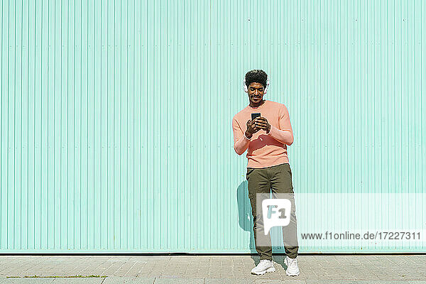 Man wearing headphones while using smart phone during sunny day