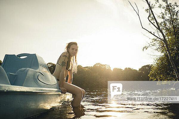 Junge Frau entspannt sich auf dem See  sitzt auf einem Boot Junge Frau entspannt sich auf dem See, sitzt auf einem Boot