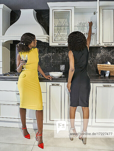 Two friends drinking red wine in the kitchen