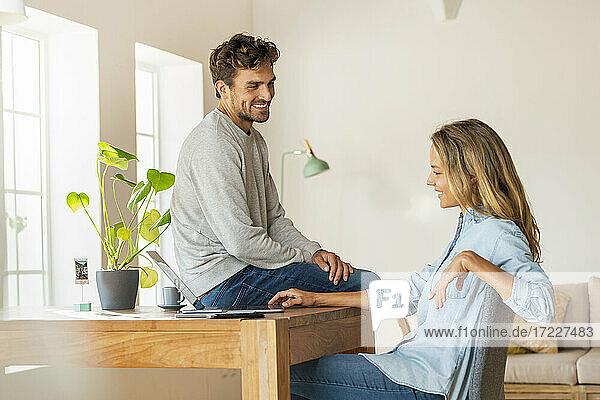 Mann diskutiert mit Freundin und schaut auf den Laptop  während er auf dem Schreibtisch im Büro sitzt